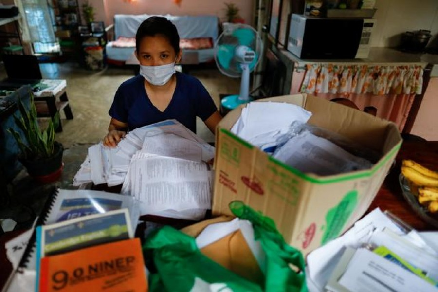 Dean, who asked that her surname not be used, is photographed at her family's home in Caloocan City, Metro Manila, Philippines on September 2, 2020, with boxes of documents she used to apply for a nursing job in the UK — Reuters/Files