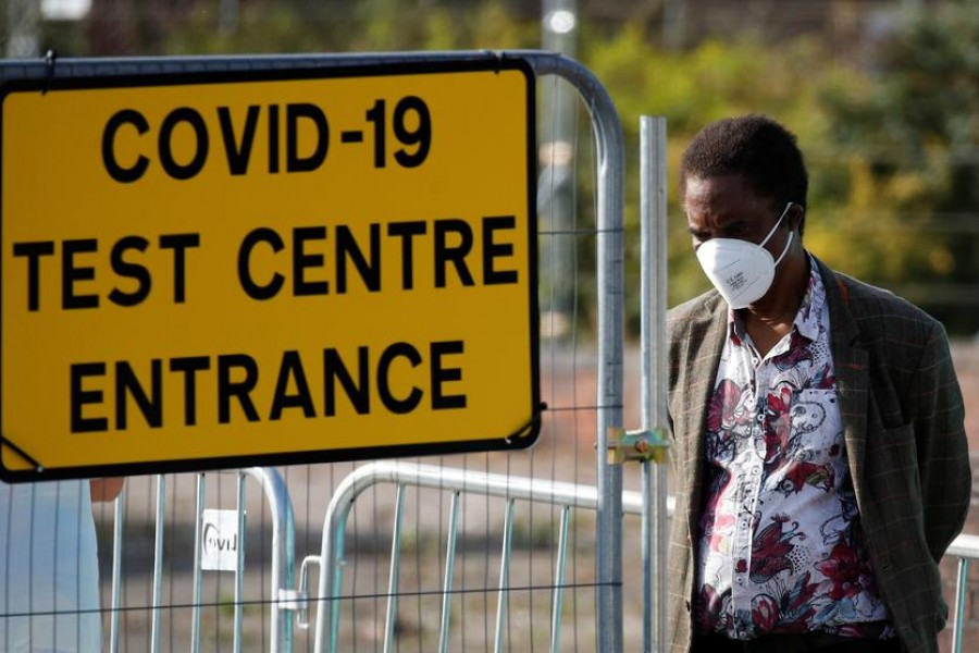 A man stands near a sign for a Covid-19 test centre amid the coronavirus disease (Covid-19) outbreak, in Bolton, Britain on September 17, 2020  — Reuters photo