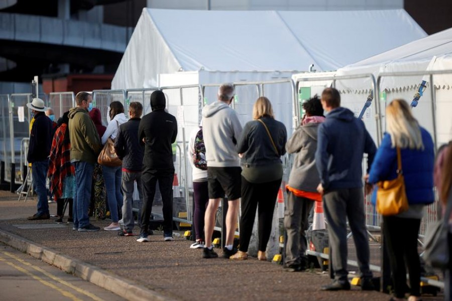 FILE PHOTO: People queue outside a test centre, following an outbreak of the coronavirus disease (COVID-19), in Southend-on-sea, Britain September 17, 2020. REUTERS/John Sibley/File Photo