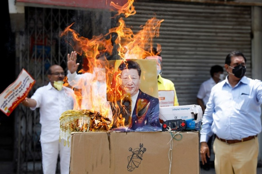 Demonstrators burn products made in China and a defaced poster of Chinese President Xi Jinping during a protest against China, in New Delhi, India, June 22, 2020. Reuters