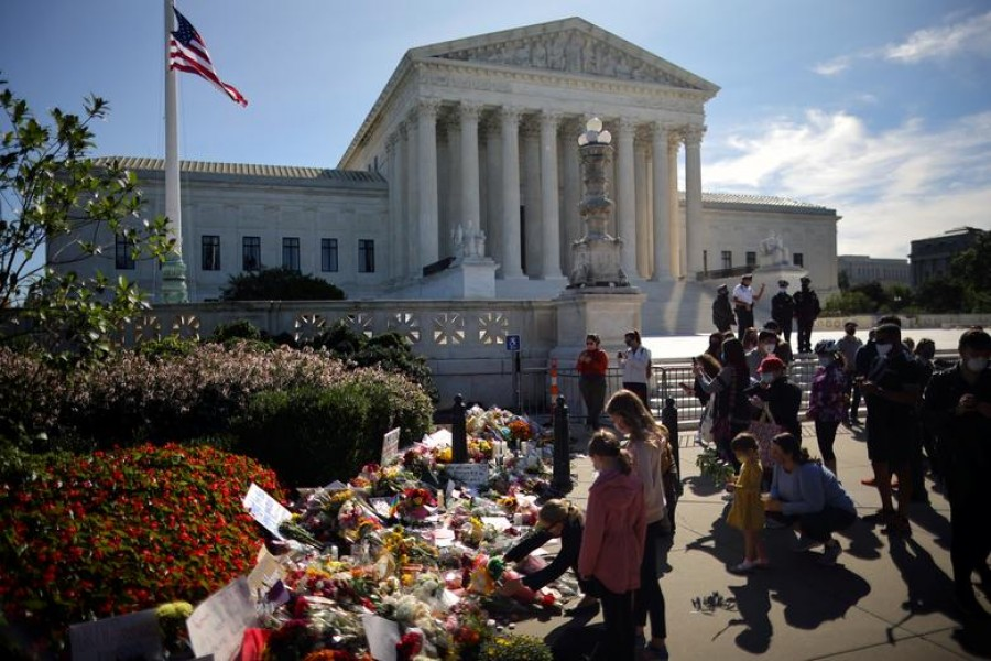 A woman puts flower on a memorial altar as people gather in front of the US Supreme Court following the death of US Supreme Court Justice Ruth Bader Ginsburg, in Washington, US, September 19, 2020 — Reuters