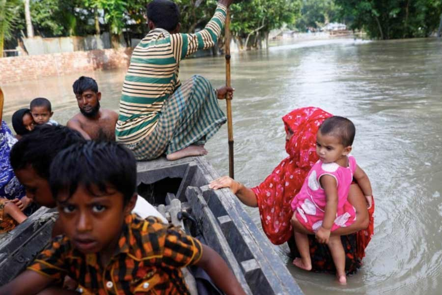 Flood-affected people getting on a boat to cross a stream in Jamalpur district on July 18 this year –Reuters Photo