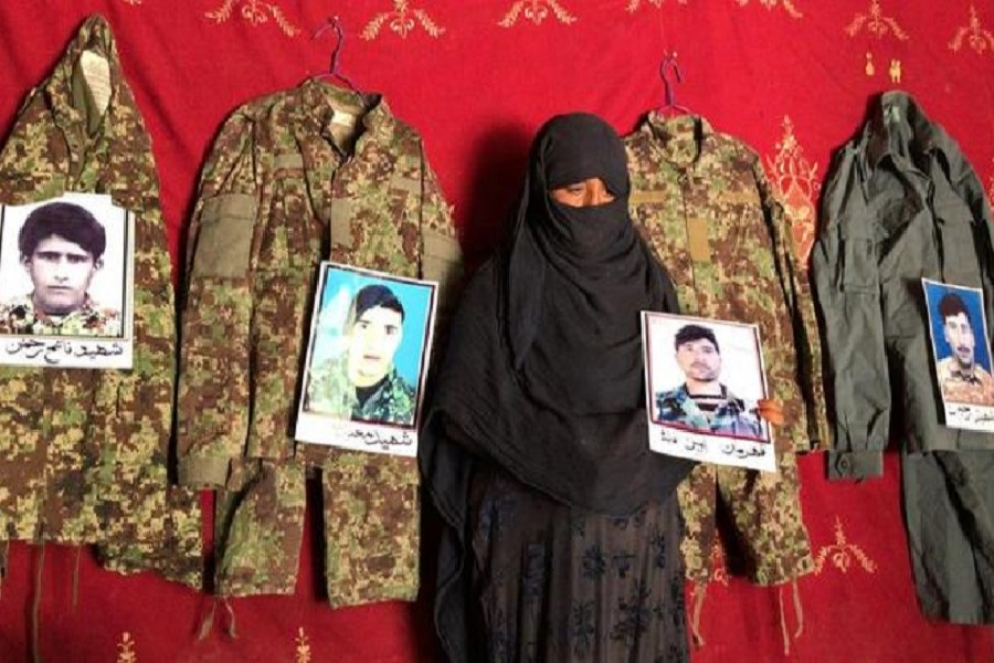 Taj Bibi 33, holds a photo of her husband next to the military uniforms and pictures of her former husbands who were killed battling the Taliban, at her home in Asad Abad, Kunar province, Afghanistan, September 20, 2020 — Reuters