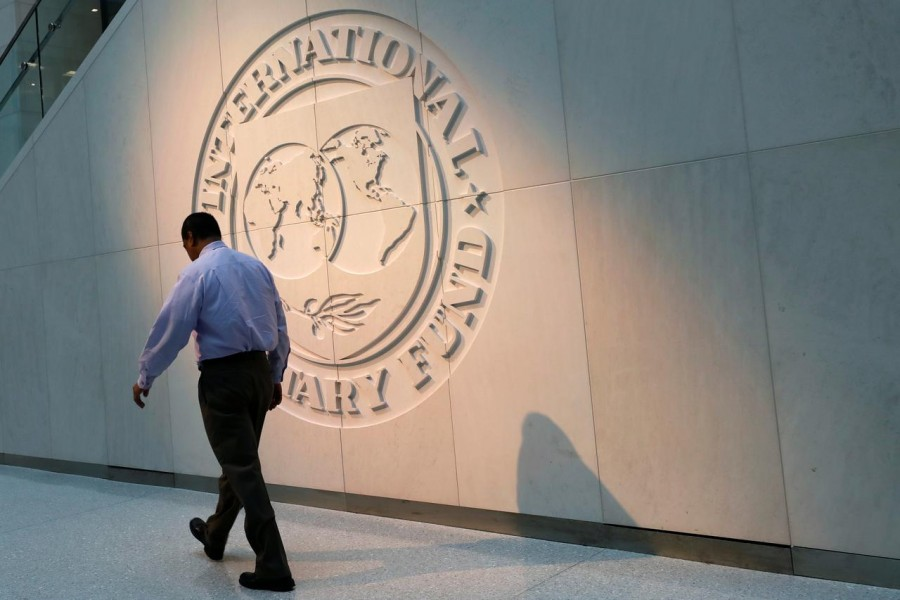 A man walks past the International Monetary Fund (IMF) logo at its headquarters in Washington, US on May 10, 2018 — Reuters/Files