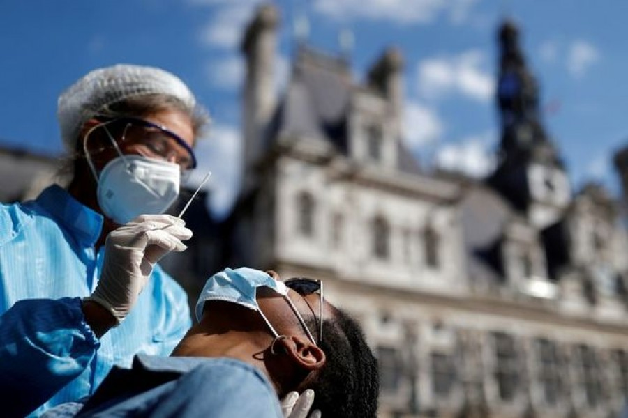 A health worker, wearing a protective suit and a face mask, prepares to administer a nasal swab to a patient at a testing site for the coronavirus disease (COVID-19) installed in front of the city hall in Paris, France, September 2, 2020. REUTERS/Christian Hartmann/File Photo