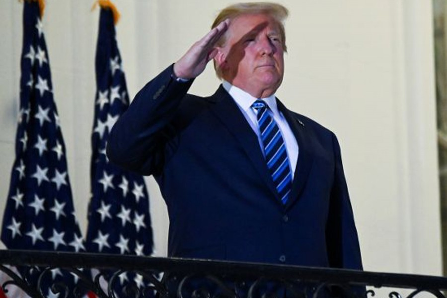 US President Donald Trump salutes as he poses without a face mask on the Truman Balcony of the White House after returning from being hospitalised at Walter Reed Medical Center for coronavirus disease (Covid-19) treatment, in Washington, US on October 5, 2020 — Reuters photo