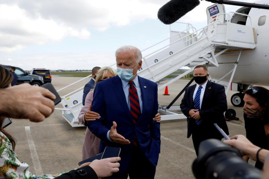 Democratic US presidential nominee Joe Biden receives a nudge from his wife, Dr Jill Biden, to remind him about proper social distancing as he speaks to reporters at Miami International Airport prior to participating in a town hall event in Miami, Florida, US on October 5, 2020 — Reuters photo