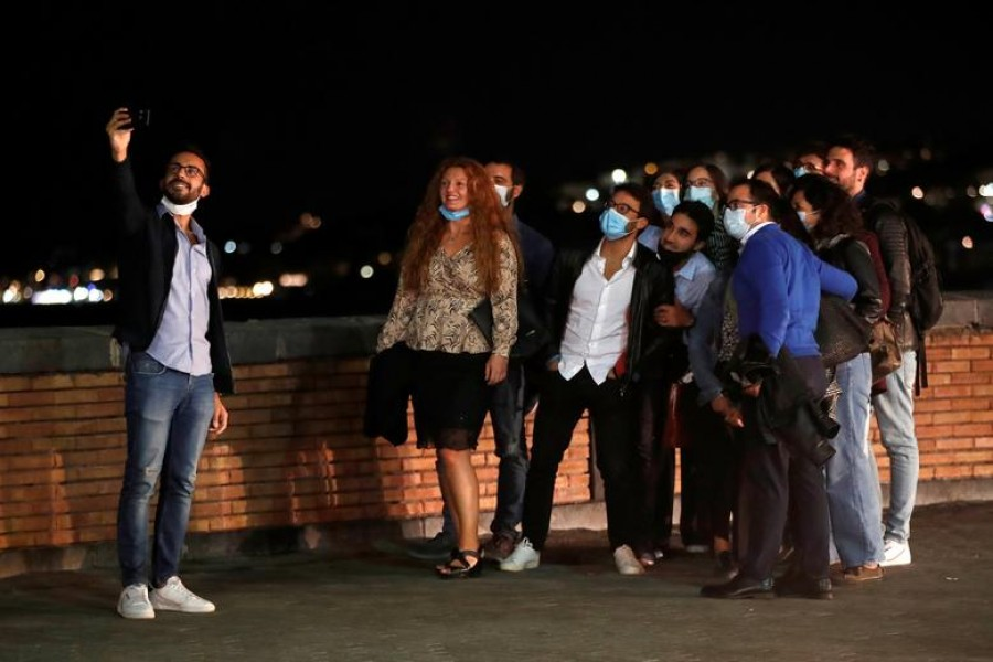 People pose for a selfie in Naples, where masks are required outdoors 24 hours a day and bars and restaurants are required to close at 11.00.p.m. (2100GMT), as part of efforts to contain the coronavirus disease (COVID-19) outbreak, Italy October 6, 2020. REUTERS/Ciro De Luca