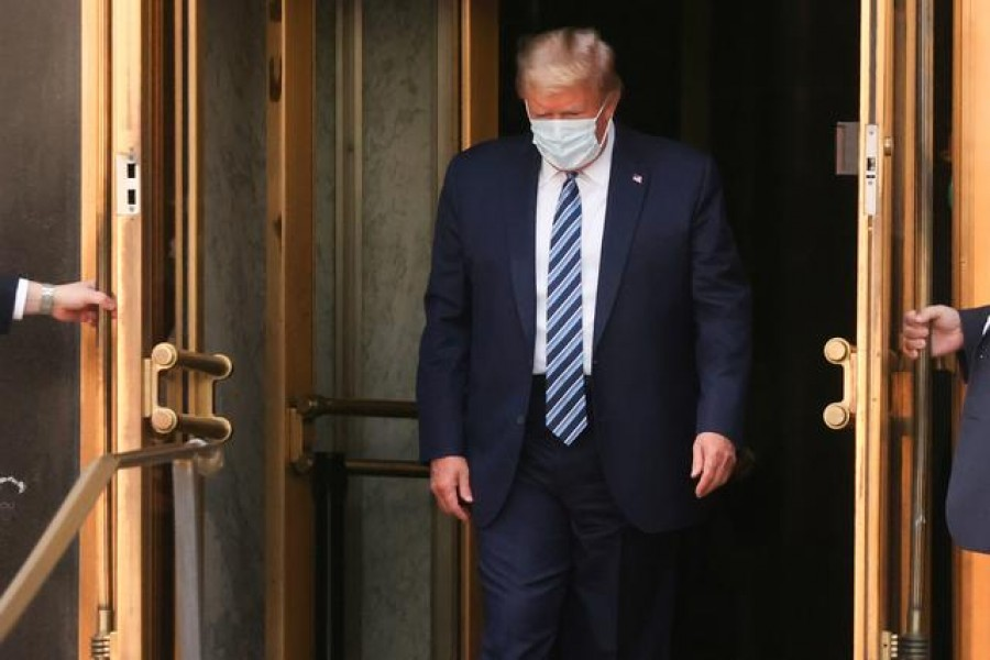 US President Donald Trump walks out the front doors of Walter Reed National Military Medical Center after a fourth day of treatment for the coronavirus disease (Covid-19) to return to the White House in Washington from the hospital in Bethesda, Maryland, US, October 5, 2020 — Reuters