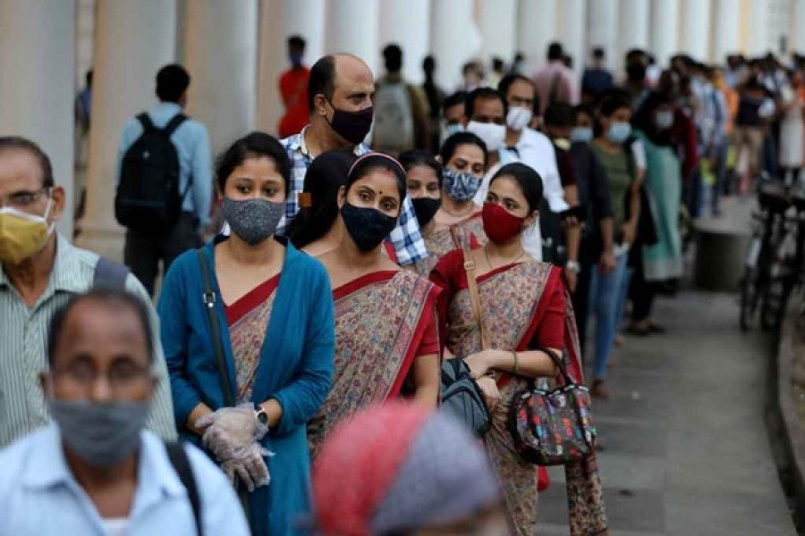 People wearing protective face masks stand in a line to enter a metro station amidst the spread of the coronavirus disease (COVID-19), in New Delhi, India, Sept 14, 2020. REUTERS