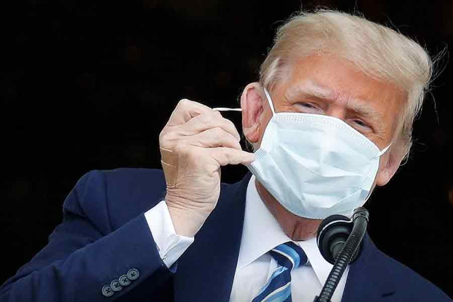 """US President Donald Trump, with bandages seen on his hand, taking off his face mask as he comes out on a White House balcony to speak to supporters gathered on the South Lawn for a campaign rally that the White House is calling a """"peaceful protest"""" in Washington, US, on Saturday –Reuters Photo"""