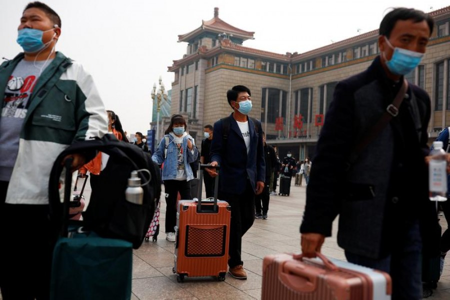 People arrive at Beijing Railway Station after an eight-day National Day holiday following the outbreak of the coronavirus disease (Covid-19) in Beijing, China, October 9, 2020 — Reuters/Files