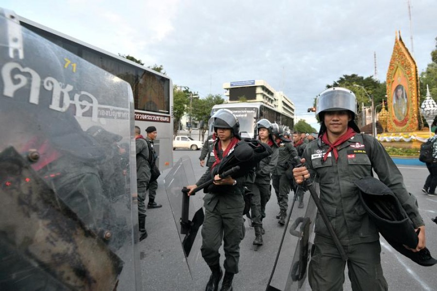 Police officers walk with their riot gear after a mass anti-government protest, on the 47th anniversary of the 1973 student uprising, in Bangkok, Thailand October 15, 2020. REUTERS/Chalinee Thirasupa