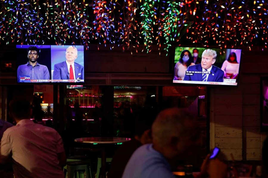 The dual town halls of US Democratic presidential candidate Joe Biden and US President Donald Trump, who are both running in the 2020 US presidential election, are seen on television monitors at Luv Child restaurant ahead of the election in Tampa, Florida, US on October 15, 2020 — Reuters photo
