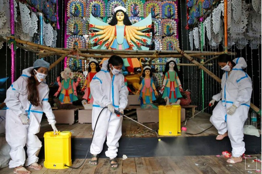 """Women wearing personal protective equipment (PPE) sanitize a """"pandal"""" or a temporary platform, ahead of Durga Puja festival, amidst the spread of the coronavirus disease (COVID-19), in Kolkata, India, October 16, 2020. REUTERS/Rupak De Chowdhuri"""
