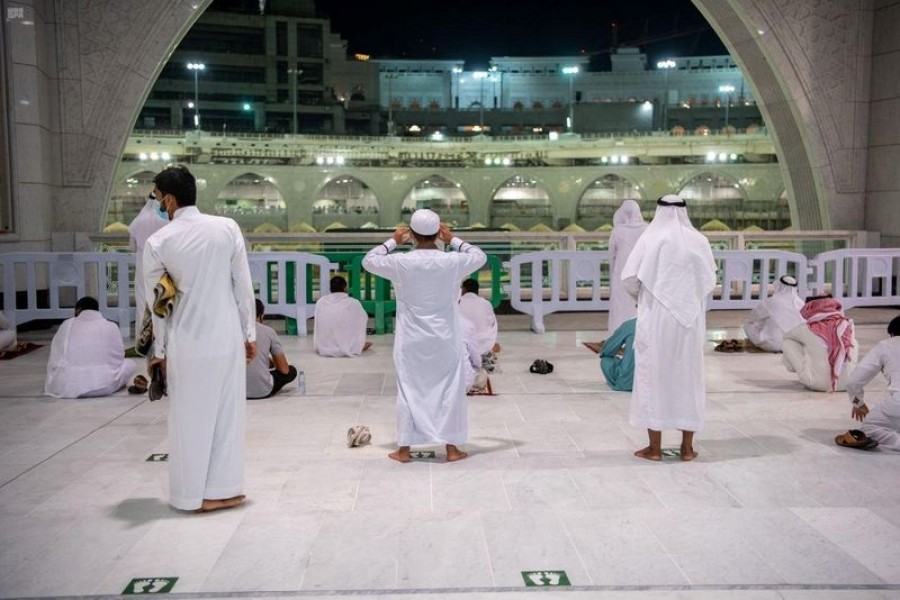 Muslims maintaining social distancing pray in the Grand Mosque for the first time in months since the coronavirus disease (COVID-19) restrictions were imposed, after they were allowed by the Saudi authorities, in the holy city of Mecca, Saudi Arabia October 18, 2020. Saudi Press Agency/Handout via REUTERS