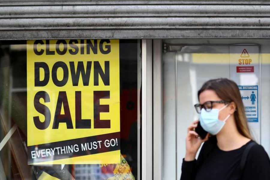 A woman wearing a protective mask speaks on the phone in front of a closed down store, as the spread of the coronavirus disease (COVID-19) continues, in London, Britain July 16, 2020. REUTERS/Hannah McKay/File Photo