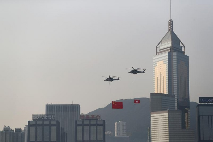 Helicopters carrying China's national flag and Hong Kong's flag fly past the skyline of Victoria Harbour on China's National Day in Hong Kong, China October 1, 2019. REUTERS/Athit Perawongmetha/File Photo