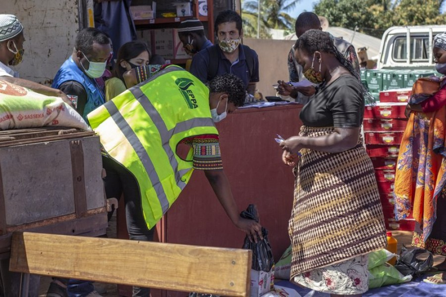 In this handout photo provided by the World Food Program on Tuesday, Sept. 22, 2020, a woman collects a monthly food parcel in Cabo Delgado Province, Mozambique, Thursday, Aug. 27, 2020.Falume Bachir/World Food Program via AP
