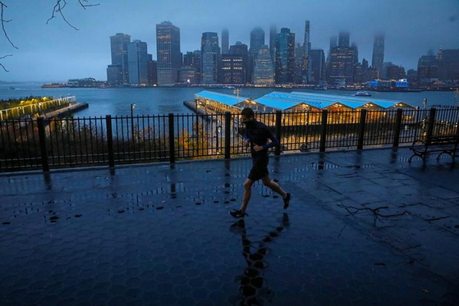 A man runs along the Brooklyn Heights Promenade as fog covers lower Manhattan in New York, U.S. November 30, 2020. REUTERS/Brendan McDermid