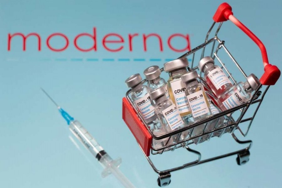 """A small shopping basket filled with vials labelled """"COVID-19 - Coronavirus Vaccine"""" and a medical sryinge are placed on a Moderna logo"""