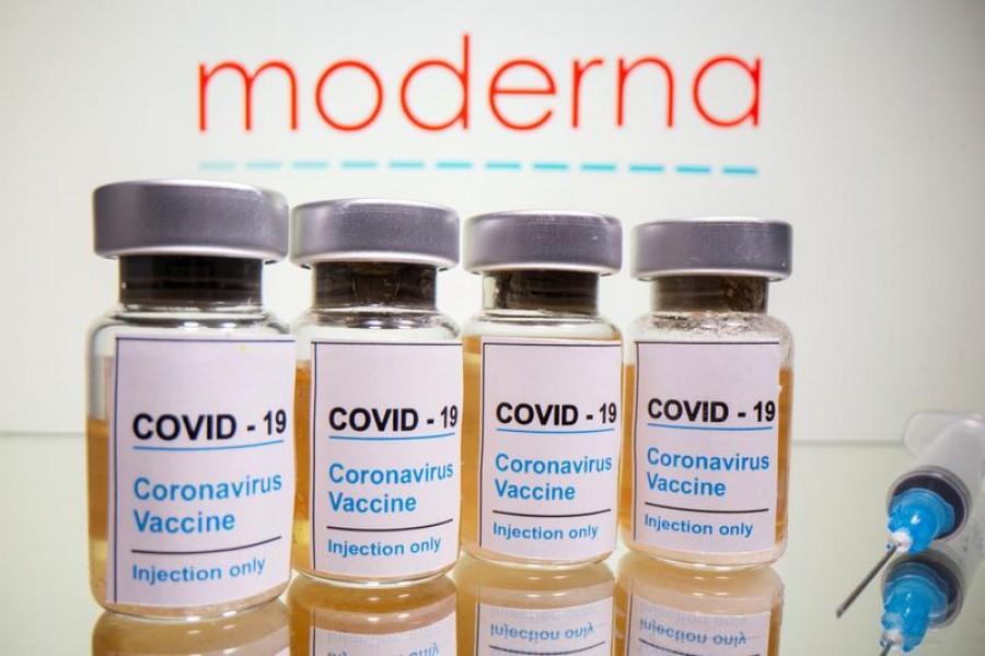 "Vials with a sticker reading, ""COVID-19 / Coronavirus vaccine / Injection only"" and a medical syringe are seen in front of a displayed Moderna logo in this illustration taken on October 31, 2020 — Reuters/Files"