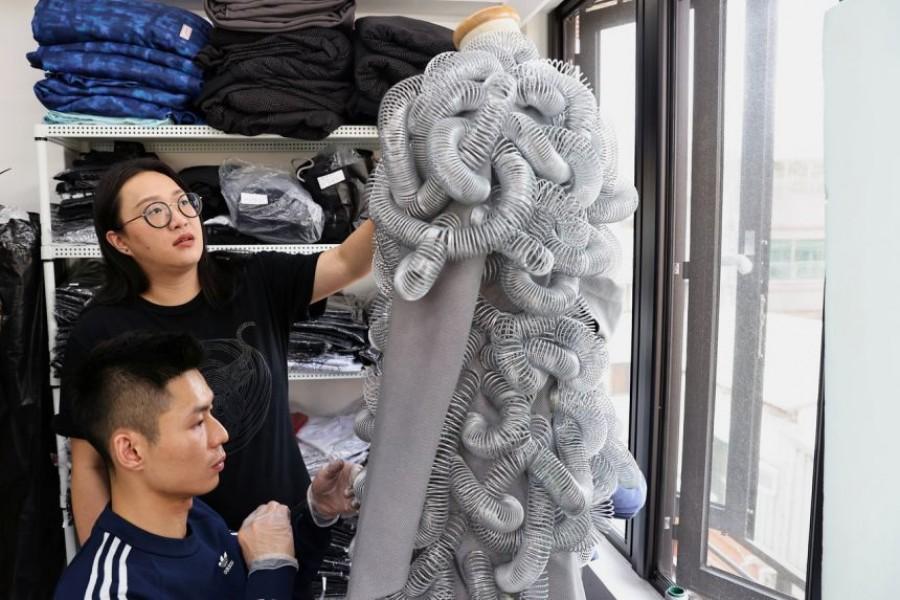 Wang Li-ling inspects a dress at her studio in Taipei — Reuters photo