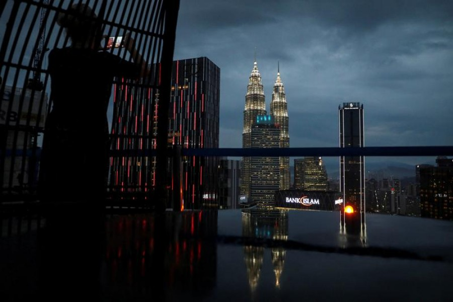 A tourist takes a picture of the city skyline at a bar in Kuala Lumpur, Malaysia, October 9, 2019. Picture taken October 9, 2019. REUTERS/Lim Huey Teng/File Photo