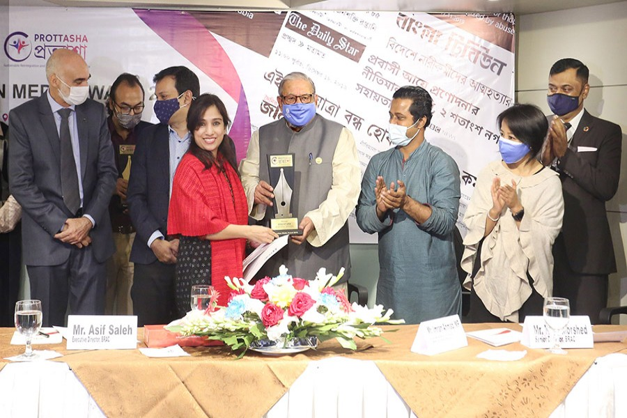 Expatriates' Welfare and Overseas Employment Minister Imran Ahmad handing over 'Migration Media Award' to Arafat Ara, a reporter of The Financial Express, in the city on Thursday