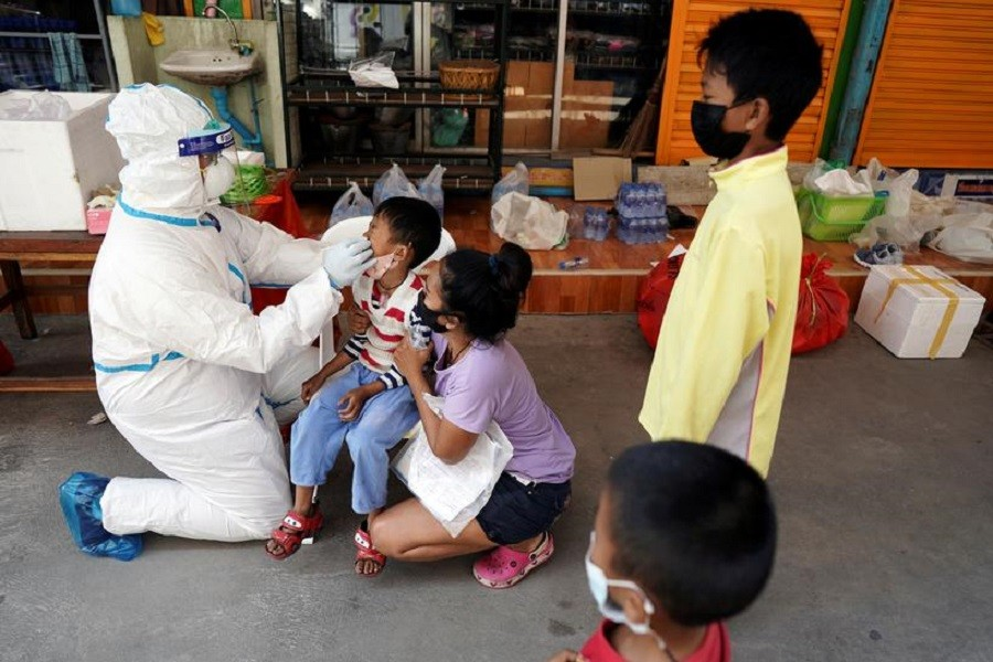 A healthcare worker takes a nasal swab sample of a child for a Covid-19 test at a migrant community, amid the coronavirus disease (Covid-19) outbreak, in Samut Sakhon province, in Thailand, December 20, 2020 — Reuters/Files