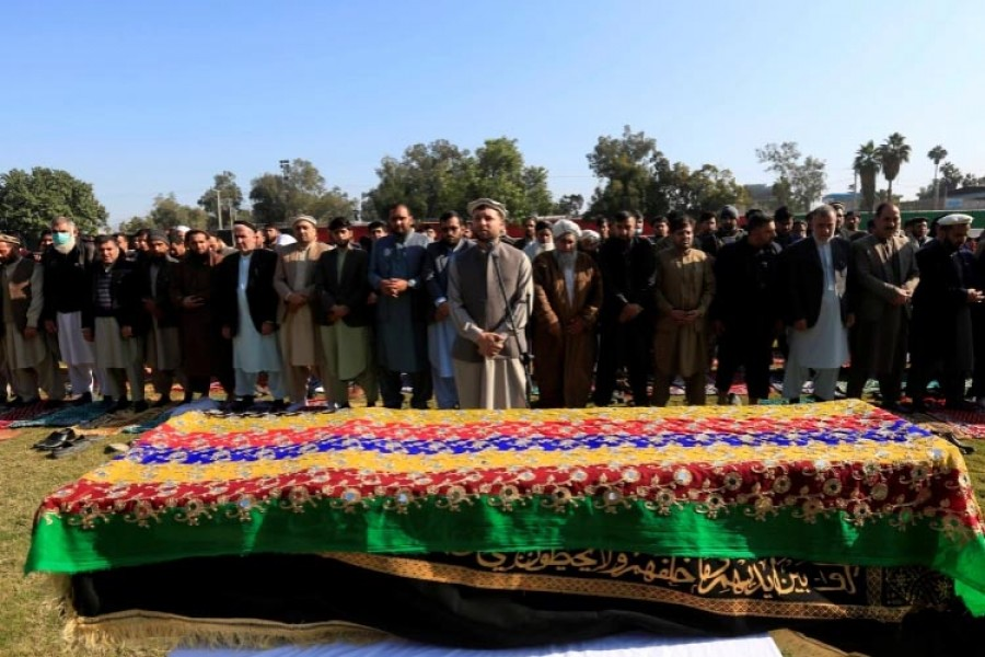 Afghan men pray near the coffin of journalist Malalai Maiwand, who was shot and killed by unknown gunmen in Jalalabad, Afghanistan, December 10, 2020 [Parwiz/Reuters]