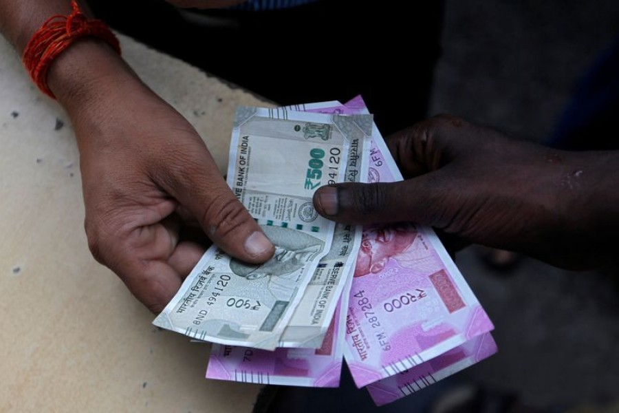 A customer hands Indian currency notes to an attendant at a fuel station in Mumbai
