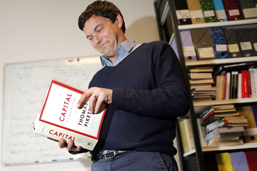 French economist and academic Thomas Piketty with his magnum opus Capital in the Twenty First Century  - Reuters