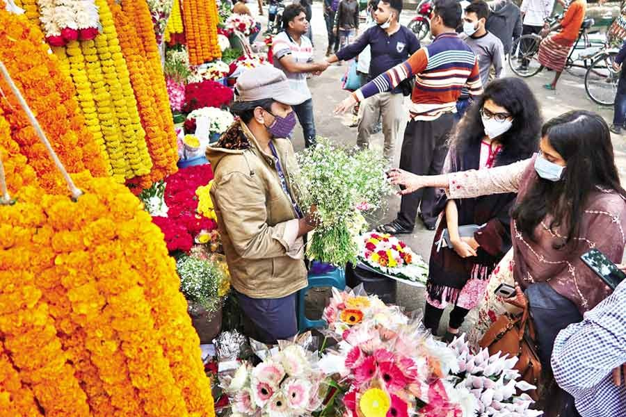 Every occasion like the New Year drives up the demand for flowers but the pandemic has made it different this year as is evident from this photo showing a handful of customers buying flowers from a shop at Shahbagh in the city on Thursday, the last day of 2020 —FE photo by Shafiqul Alam