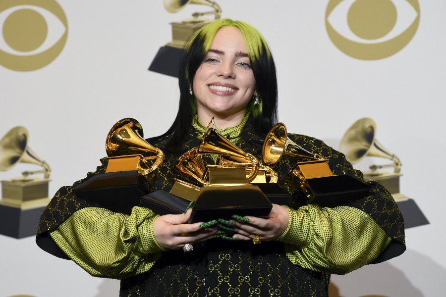 """Billie Eilish poses in the press room with the awards for best album and best pop vocal album for """"We All Fall Asleep, Where Do We Go?"""", best song and record for """"Bad Guy"""" and best new artist at the 62nd annual Grammy Awards at the Staples Center on Sunday, Jan. 26, 2020, in Los Angeles. (AP Photo/Chris Pizzello)"""