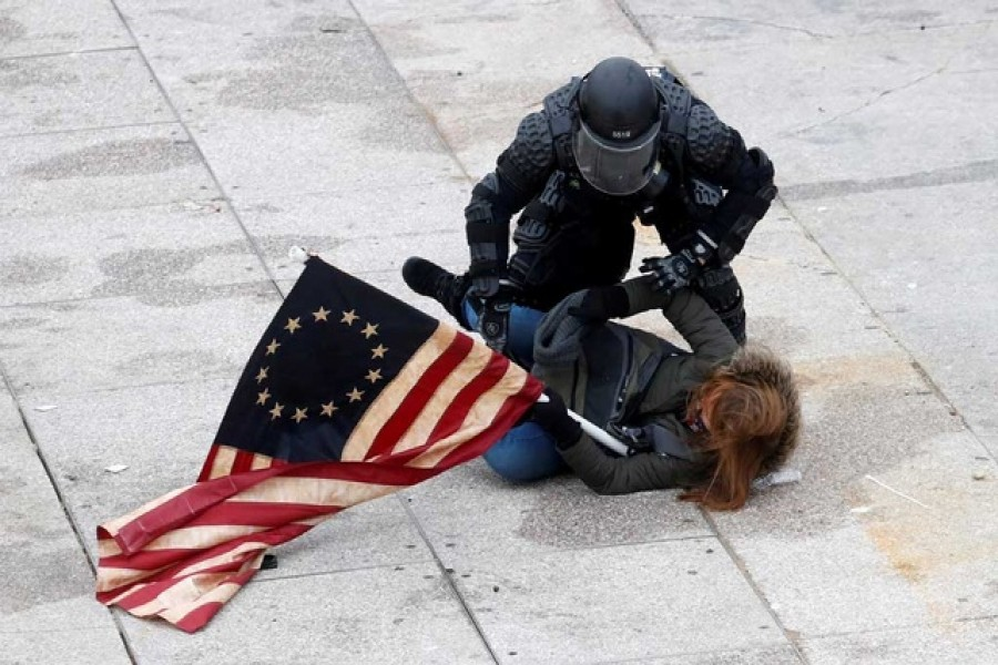 A police officer detains a pro-Trump protester as mobs storm the US Capitol, during a rally to contest the certification of the 2020 US presidential election results by the US Congress, at the US Capitol Building in Washington, US, January 6, 2021. REUTERS/Shannon Stapleton