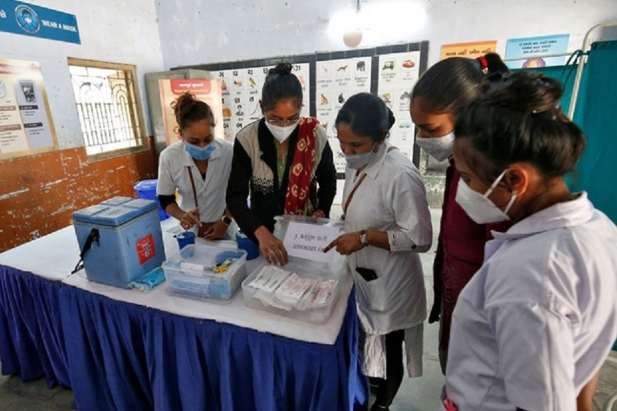 Health workers prepare a vaccination room inside a classroom of a school, which has been converted into a temporary COVID-19 vaccination centre in Ahmedabad, India, January 4, 2021. Reuters