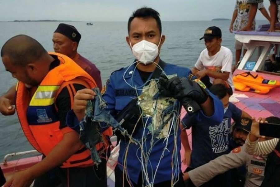 A member of the rescue team looking for an Indonesian plane that lost contact after taking off from the capital Jakarta holds suspected debris, at sea, January 9, 2021, in this picture obtained from social media. INSTAGRAM @HUMASJAKFIRE/via REUTERS