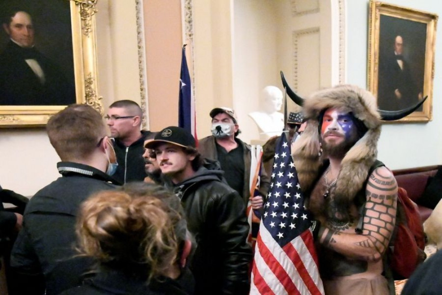 Jacob Anthony Chansley, also known as Jake Angeli, of Arizona, stands with other supporters of U.S. President Donald Trump as they demonstrate on the second floor of the U.S. Capitol near the entrance to the Senate after breaching security defenses, in Washington, U.S., January 6, 2021. REUTERS/Mike Theiler/File Photo