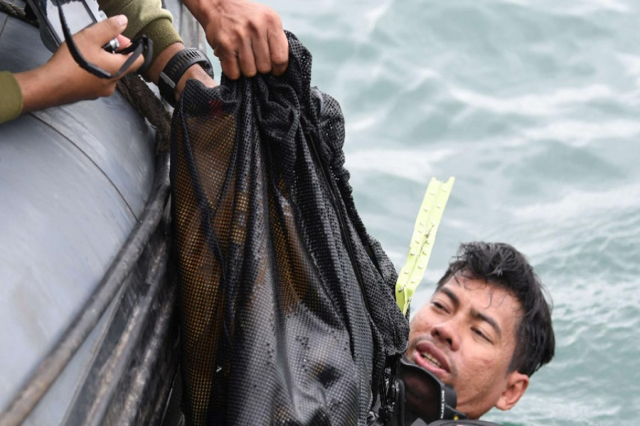 Indonesia Navy diver recovers what are believed to be remains from Sriwijaya Air Flight SJ182, which crashed into the sea off the coast of Jakarta, Indonesia, January 10, 2021 in this photo taken by Antara Foto/M Risyal Hidayat via REUTERS