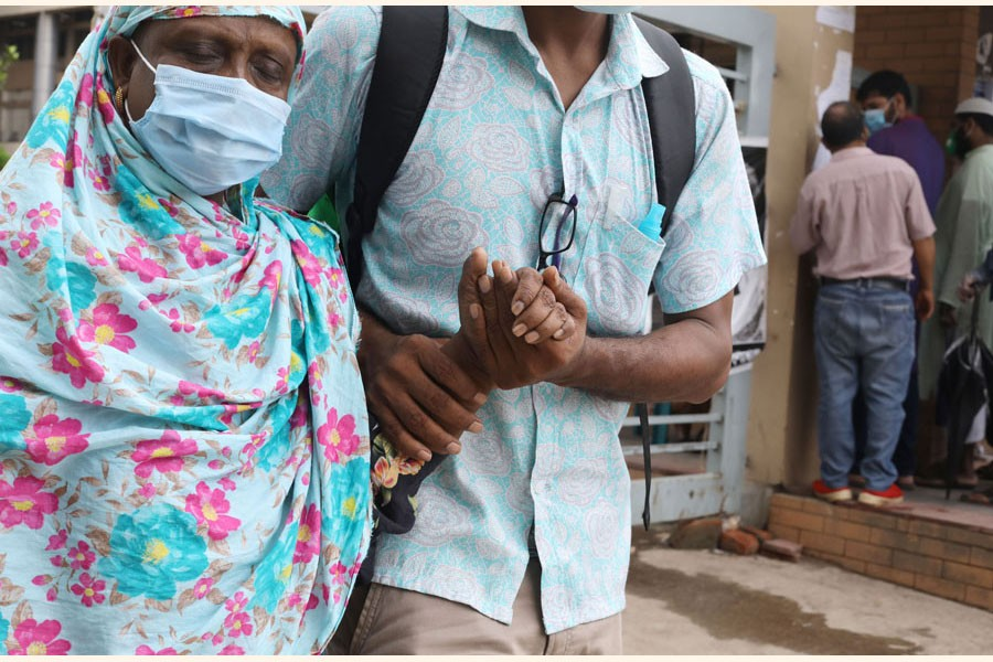 A woman with the support of her son leaving a hospital in Dhaka after giving sample for Covid-19 test  - FE Photo