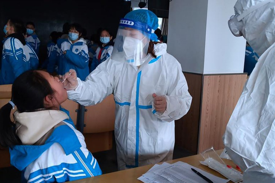 A medical worker in a protective suit collects a swab sample from a middle school student during a mass nucleic acid testing following a recent coronavirus disease (Covid-19) outbreak in Xingtai, Hebei province, China on January 6, 2021. China Daily via REUTERS/Files