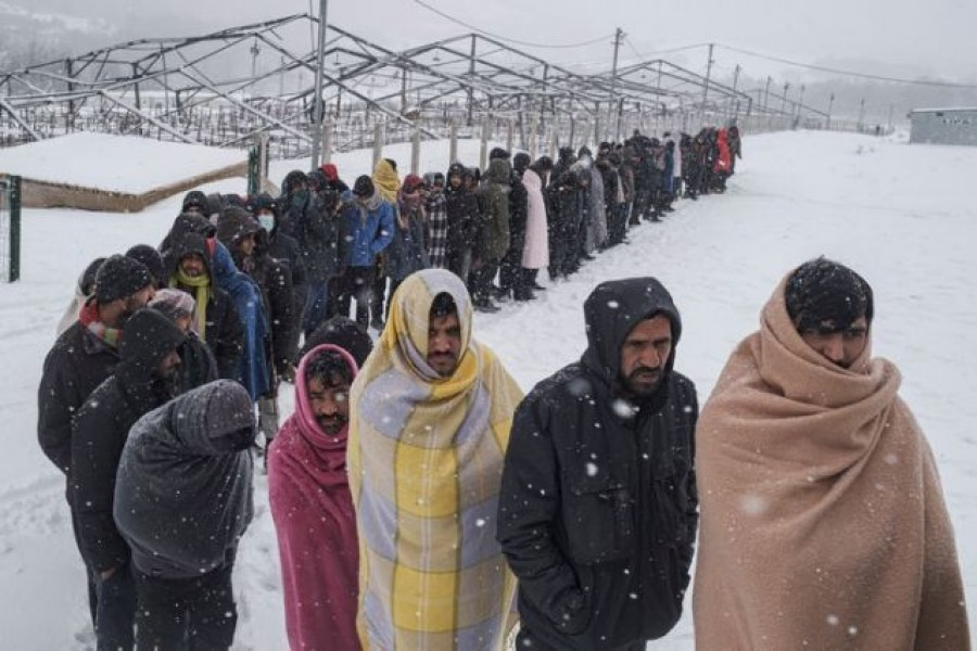 Migrants queue to receive food during a snowfall as hundreds of them are taking shelter in abandoned buildings in the northwestern town of Bihac in Bosnia and Herzegovina, January 11, 2021. REUTERS/Marko Djurica