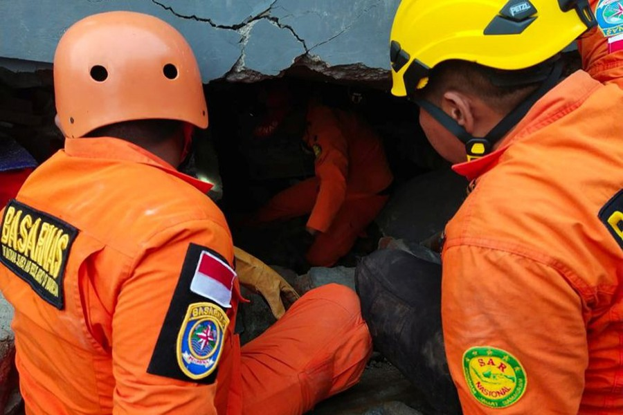 Members of a search and rescue agency team dig through rubble after an earthquake, in Mamuju, West Sulawesi Province, Indonesia January 15, 2021 — Basarnas Sulbar via REUTERS