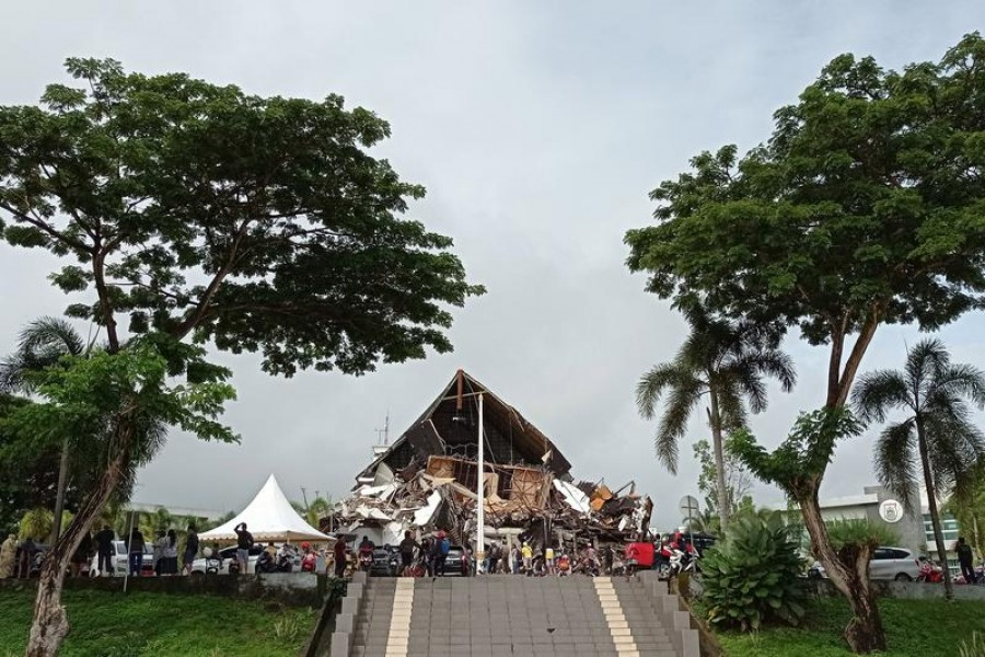 People look at the damaged governor of West Sulawesi province's office following an earthquake in Mamuju, West Sulawesi province, Indonesia, January 15, 2021 in this photo taken by Antara Foto –Antara Foto/Akbar Tado/via Reuters