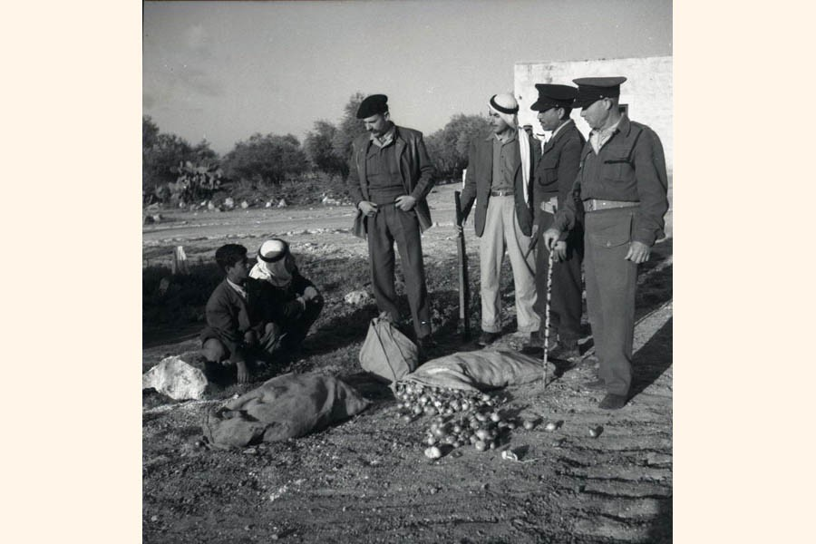 Israeli military policemen inspect a suspicious sack of onions found in possession of Arab citizens, in 1952