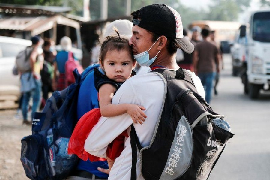A man kisses his daughter as he takes part with other Hondurans in a new caravan of migrants, set to head to the United States, in Cofradia, Honduras, January 15, 2021 — Reuters