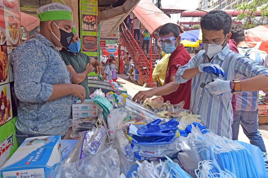 Street vending is an example of informal economy. People buy face masks and sanitary products from street vendors in Dhaka —Xinhua photo