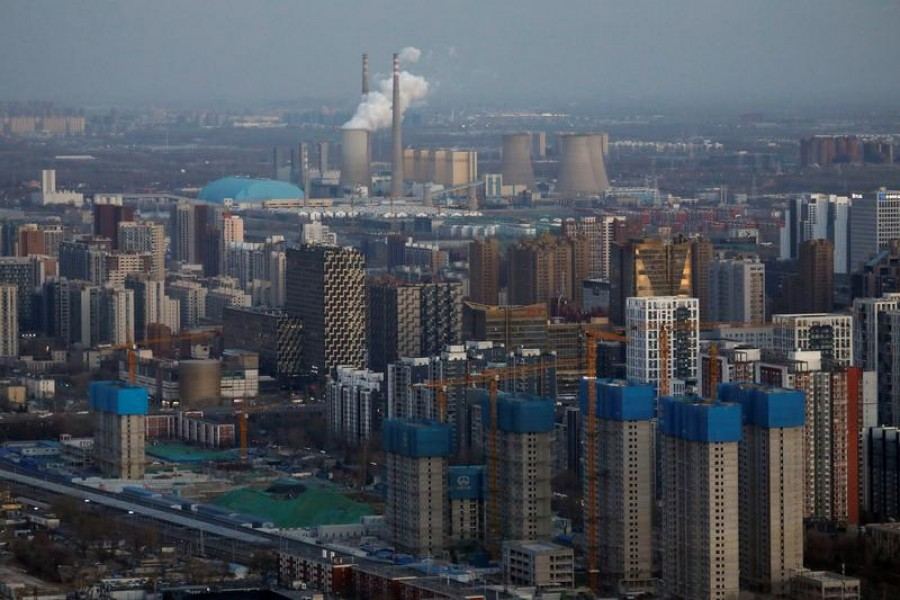 Residential buildings under construction and a power station are seen near the central business district in Beijing, China, January 15, 2021 — Reuters