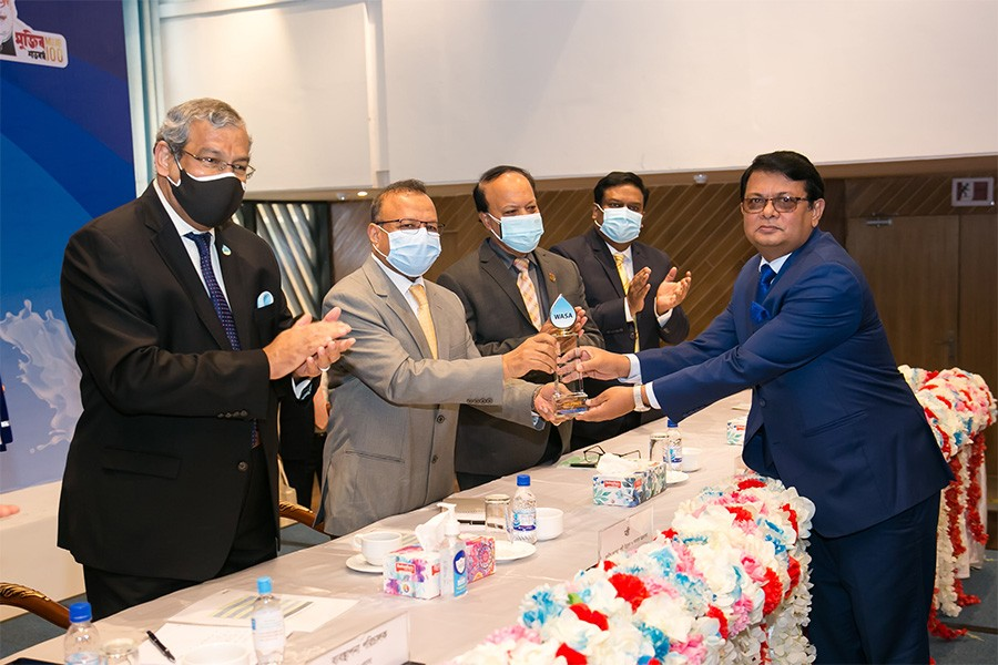 Local Government, Rural Development and Cooperatives Minister Md Tazul Islam handing over a crest to Managing Director and also CEO of Premier Bank Limited M Reazul Karim, FCMA, in the city on Monday